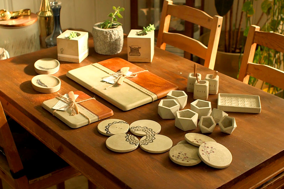 Mona's concrete homewares, including cheese boards, coasters, and vases.